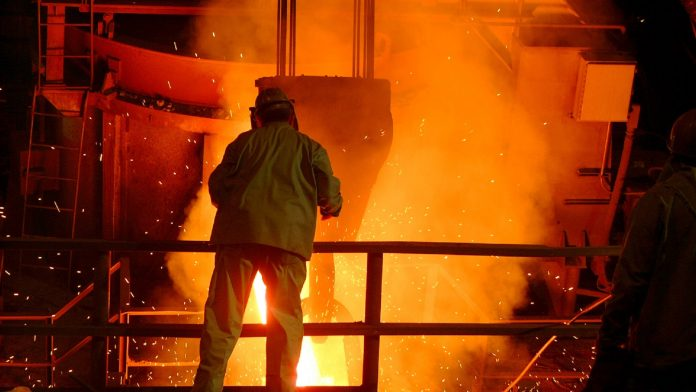 Steel mill worker over furnace