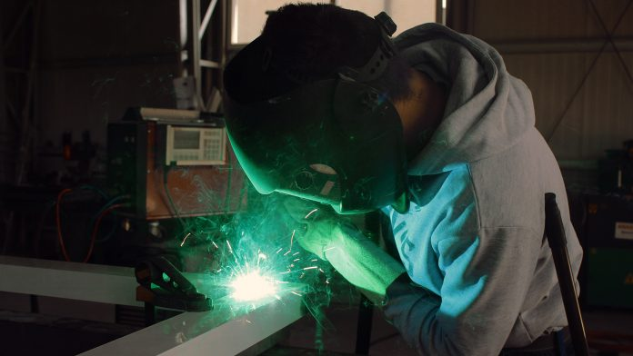 Welder in manufacturing facility
