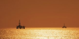 Two offshore oil rigs during sunset