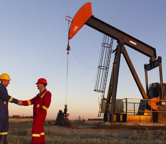 Oil field workers in front of oil derrick